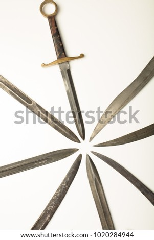 Isolated old dagger with assorted blades of weapons all pointing to a central point with copy space to form a converging pattern