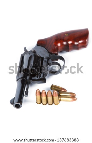 Isolated old revolver handgun with bullets, studio shot - stock photo