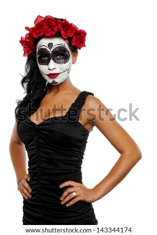 Isolated on a white background, this beautiful young woman shows off her sugar skull makeup. - stock photo