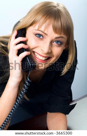 Isolated on white portrait of smiling beautiful blond businesswoman gazing at the camera talking by her phone