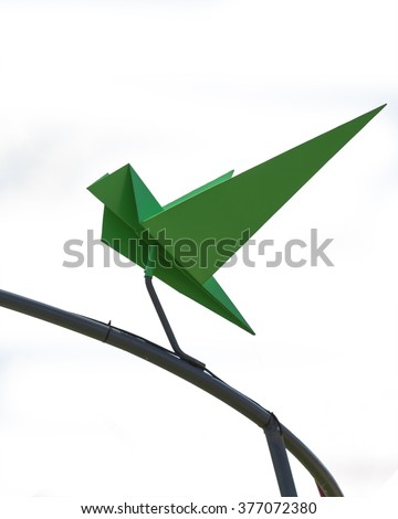 Isolated origami bird with stick on steel looks like flying with white background - stock photo