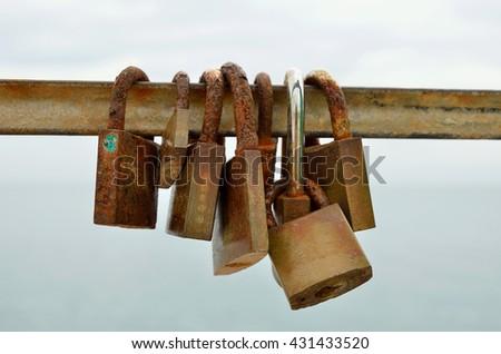 isolated padlocks closed on an iron bar - stock photo