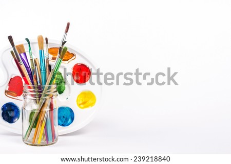 isolated paints palette and paints brushes in a glass - stock photo