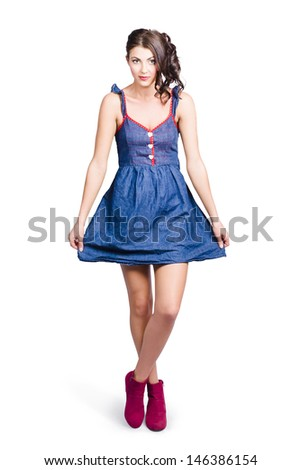 Isolated photo of a lovable eighties female pin-up curtseying in blue denim dress. 80s glamour style - stock photo