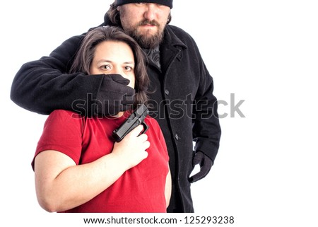 Isolated photo of a woman in red shirt being assaulted from behind by white male in  black coat, hat and gloves. The mans hand is covering the woman's mouth with fear in her eyes. copy space for text - stock photo