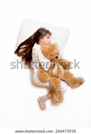 Isolated photo of cute girl lying in bed and hugging teddy bear - stock photo