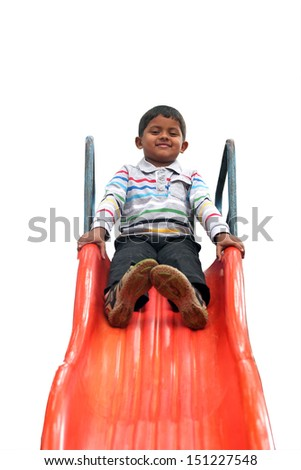Isolated photo of handsome indian boy ( kid ) on slider at a park. The isolated photo with white background & clipping path shows summer time playground with a schoolboy playing on a slider  - stock photo