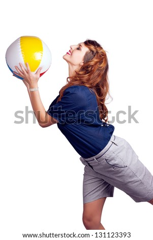 Isolated Picture Of A Playful Brunette Woman Throwing Colourful Beach Ball In A Summer Fun Concept