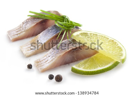 isolated pieces of salt fillet herring with lime - stock photo