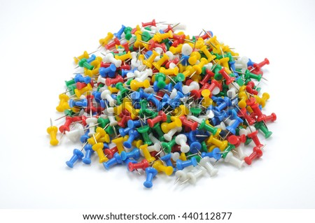 Isolated pile of colorful office push pins scatter around on white background.