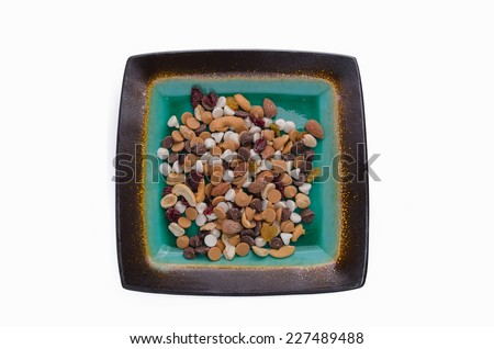 Isolated Plate of Trail mix with nuts, chocolate chips, cashews, raisins and more - stock photo