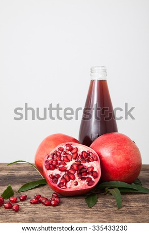 Isolated pomegranate juice with pomegranate, leaf, and seed on white background