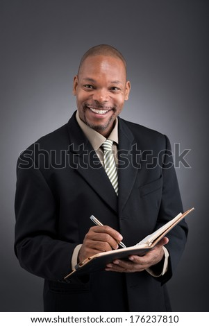 Isolated portrait of a black cheerful businessman in formal making notes and looking at camera