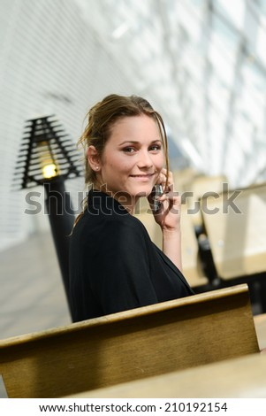 isolated portrait of a cheerful young business woman making a phone call in a public station - stock photo