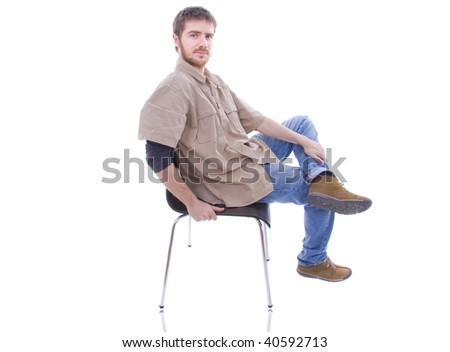 Isolated portrait of a young handsome casual man relaxing in a chair.