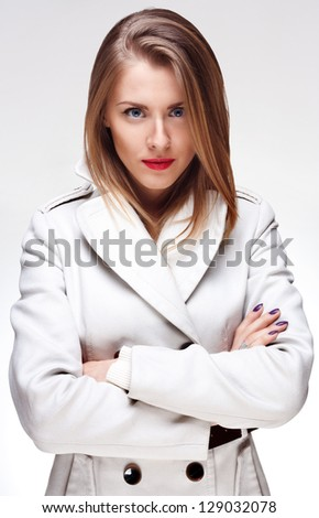 Isolated portrait of a young woman with confident look standing in a stylish coat. - stock photo