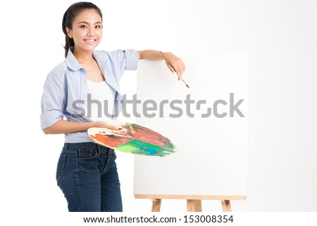 Isolated portrait of an artist standing near the empty canvas ready to draw  - stock photo