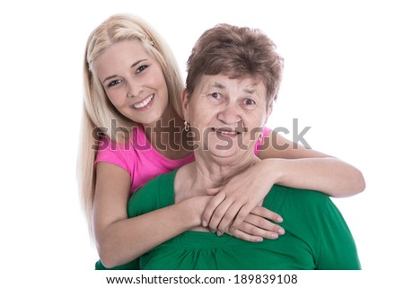 Isolated portrait of blond granddaughter hugging her grandmother.
