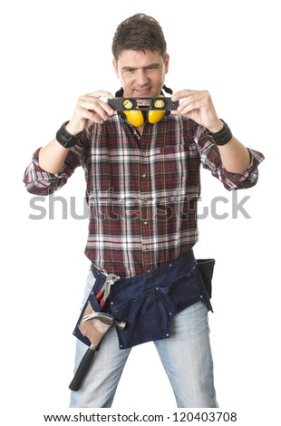 Isolated portrait of carpenter looking at level and wearing tool belt