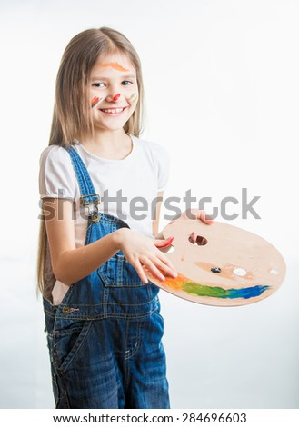 Isolated portrait of cute artist girl with face in paint