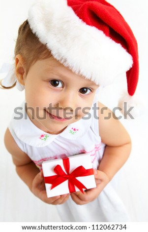 Isolated portrait of little cute girl with Christmas present - stock photo