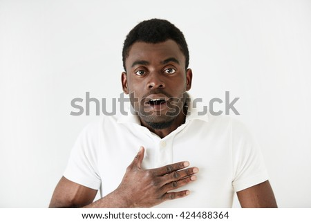 Isolated portrait of shocked young attractive African American male looking in full disbelief, hand on chest, surprised with some unexpected news. Positive human emotions and facial expressions - stock photo