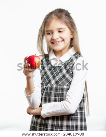 Isolated portrait of smiling schoolgirl looking at red apple - stock photo