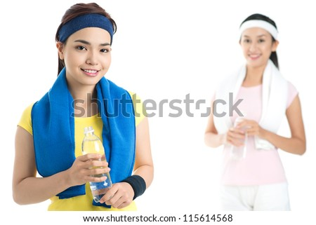 Isolated portrait of sportive young ladies resting after their usual workout - stock photo