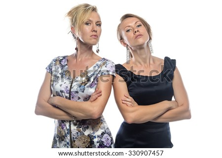 Isolated portrait of two serious sisters. Isolated photo on white background.