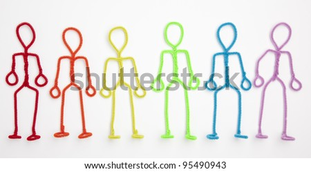 Isolated rainbow colored pipe cleaner stick figures standing with arms at their sides.