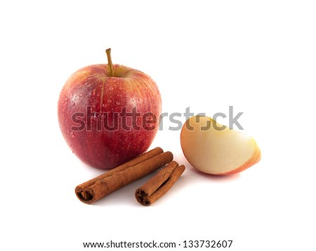 Isolated red apple with slices and cinnamon sticks (white background). Fresh diet fruit (water drops). Healthy fruit with vitamins.