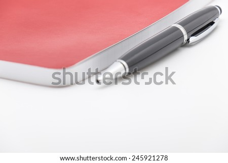 Isolated red leather notebook or organizer with ballpoint pen on white background - stock photo