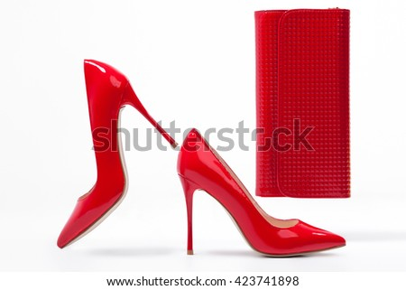 isolated red stylish stiletto shoes with clutch bag; studio shot of classic woman footwear and accessories; - stock photo