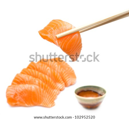 Isolated salmon sashimi set with chopsticks holding a piece of sliced salmon - stock photo