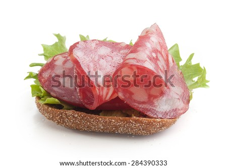 Isolated sandwich with smoked sausages, fresh green lettuce and rye bread