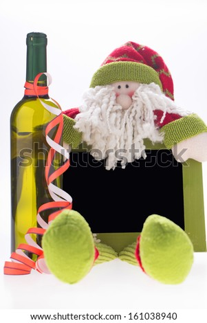 isolated Santa Claus figurine with plat and wine bottle on white background - stock photo