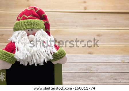 isolated Santa Claus figurine with plat on wooden - stock photo