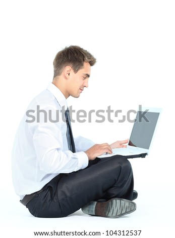 Isolated seated young businessman using a laptop