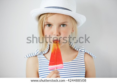 Isolated shot of cute little girl with green eyes and blonde hair, wearing white hat and striped dress, holding fruit ice cream. Portrait of Caucasian child licking popsicle and looking at the camera - stock photo