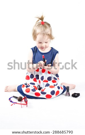 Isolated shot of little fashionista playing with a lipstick, brush for powder and other mommy's stuff - stock photo