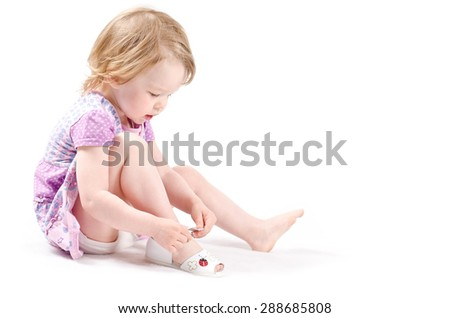 Isolated shot of little fashionista trying on new shoes - stock photo