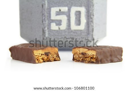Isolated shot of protein bar with a 50 pound dumbbell in the background. - stock photo