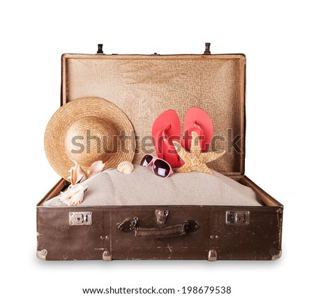 Isolated shot of retro suitcase with accessories on beach - stock photo