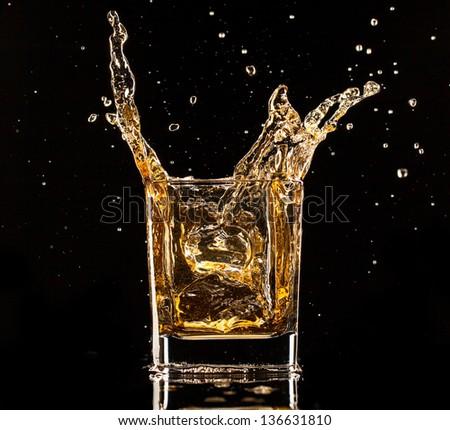 Isolated shot of whiskey splashing out of glass on black background - stock photo