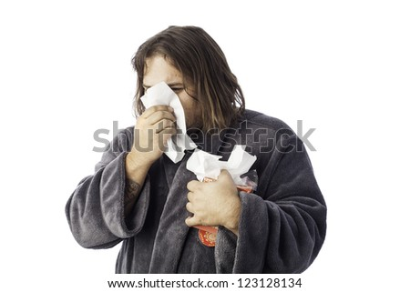 isolated sick man bundled up in a robe sneezing into a tissue