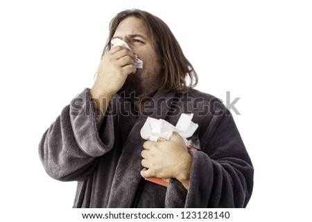 isolated sick man bundled up in a robe sneezing into a tissue - stock photo