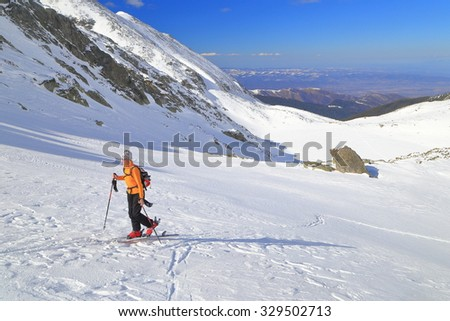 Isolated ski mountaineer climbs moderate slope on snow covered mountain
