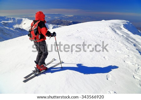 Isolated ski mountaineer climbs snow covered mountain plateau - stock photo
