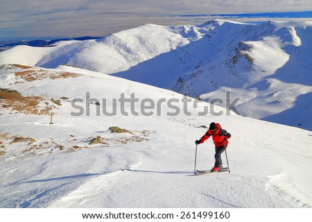Isolated ski mountaineer putting serious effort while skinning up a steep slope - stock photo