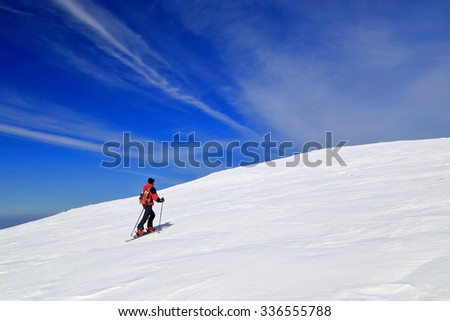 Isolated ski mountaineer traversing a vast slope covered with snow in winter - stock photo
